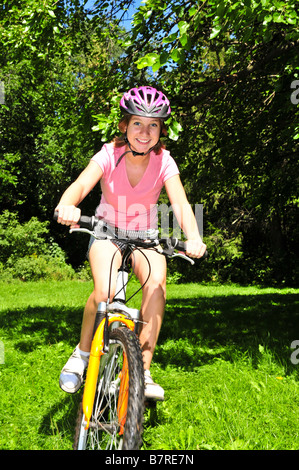 Portrait of a teenage girl riding a bicycle in summer park outdoors - Stock Photo
