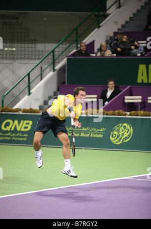German star Philipp Kohlschreiber serving in the Qatar Open against Roger Federer - Stock Photo