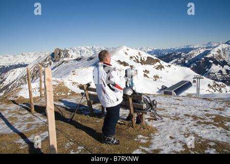 Pinzgau Region Austria EU January Male and female skiers at a viewpoint above Gipfelbahn gondola station taking - Stock Photo