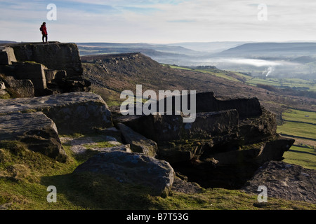 Walker on the Great Buttress, Curbar Edge, Derwent Valley, Peak District National Park, Derbyshire, England - Stock Photo