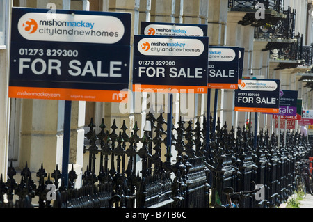 An abundance of For Sale sign boards on railings on Holland Road Hove in the City of Brighton Hove East Sussex - Stock Photo