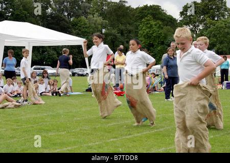 Children doing the sack race, Primary school Sports Day, UK - Stock Photo