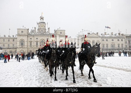 The Household Cavalry riding throug the snow across Horseguards Parade for duties at Buckingham Palace after a change - Stock Photo
