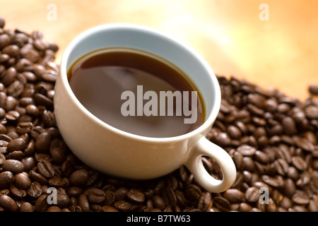 A cup of coffee sitting on coffee beans - Stock Photo