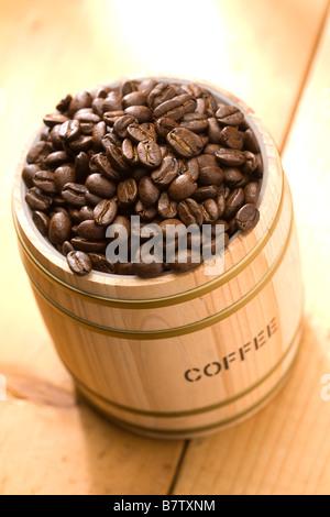 Coffee bean in oak drum sitting on wood floor - Stock Photo
