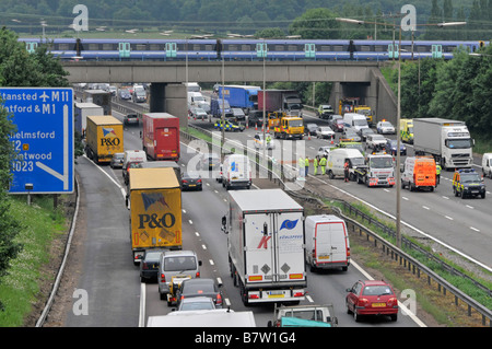 M25 motorway slow traffic accident being cleared clockwise carriageway with passenger train on bridge - Stock Photo