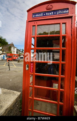 traditional red telephone box offering email and texting services in village of Polperro, Cornwall, UK - Stock Photo