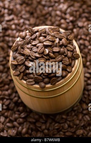 Coffee bean in oak drum sitting on beans - Stock Photo