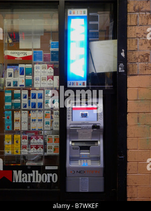 An outdoor automatic teller machine beneath a lighted 'ATM' sign next to a window display full of cigarettes in - Stock Photo