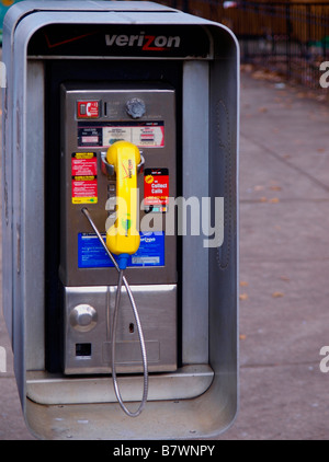 Dirty, colorful pay telephone looking old-fashioned in a modern urban setting. - Stock Photo