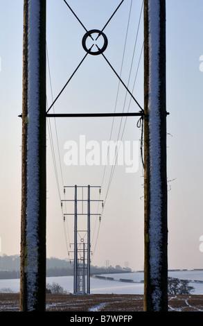 Power lines crossing farmland in winter, UK - Stock Photo