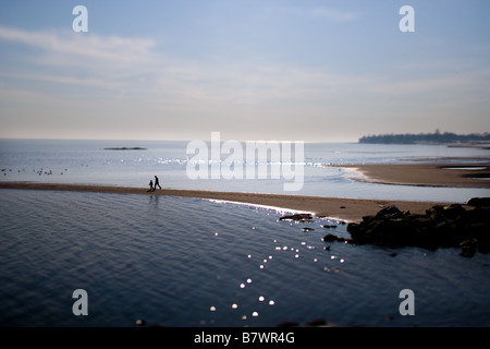 A father and son walks along the beach in West Haven Connecticut USA during the winter - Stock Photo