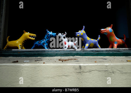 Line of ceramic dog figurines on window sill - Stock Photo
