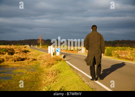 A man walking along a road in the New Forest, Hampshire. UK. Evening sun behind causing long shadows.  Dark clouds - Stock Photo
