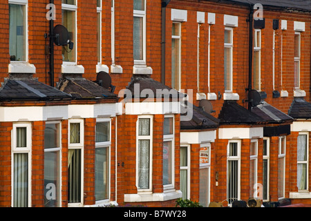 Red brick terraced housing with bay windows - Stock Photo