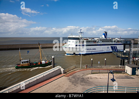 Frisian Islands ferry leaving harbour as fishing boat enters with the Wadden sea behind Harlingen Friesland Netherlands - Stock Photo