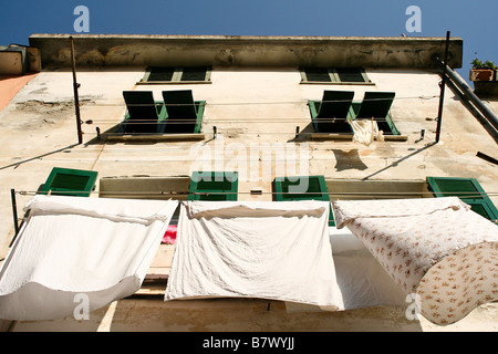 Looking up at sheets hanging to dry on an old house with green shutters set against a blue sky. - Stock Photo