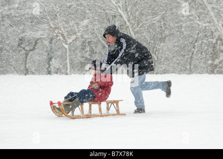 Winter fun: Man pushing a young boy on a sledge in the snow, Cheam, (south London), Surrey, England - Stock Photo