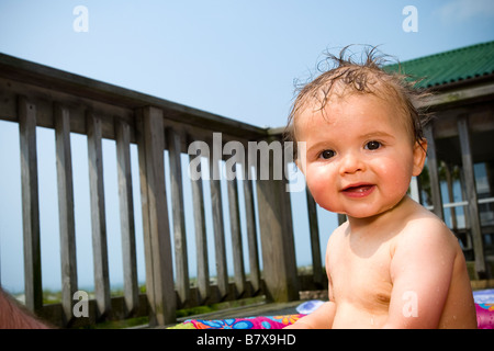 baby in baby swimming pool smiling, portrait - Stock Photo
