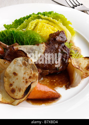 A plate of traditional Lancashire hotpot with Savoy cabbage