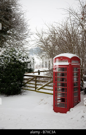 UK red telephone box in remote Wiltshire village location covered in snow. Adjacent to traditional five bar wooden - Stock Photo
