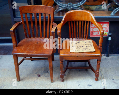 Two Old Wooden Chairs On A City Sidewalk Holding Handwritten Cardboard For Sale Sign