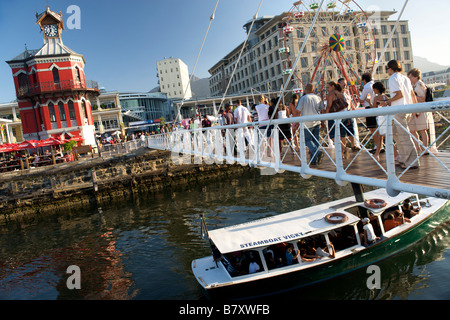 Small boat passing under the pedestrian bridge at the clock tower in Cape Town's Victoria and Alfred waterfront. - Stock Photo