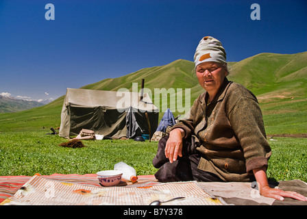 Kyrgyz woman outside a tent drinking horse milk Kyrgyzstan - Stock Photo