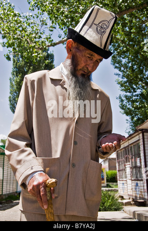 Old Kyrgyz man dressed with typical hat and walking stick watching the time Kochkor Kyrgyzstan - Stock Photo