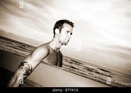 Surfer at beach holding surfboard walking, portrait - Stock Photo