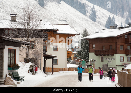 Rauris Raurisertal Austria Europe January Traditional chalets and people in Alpine ski resort with snow in winter - Stock Photo