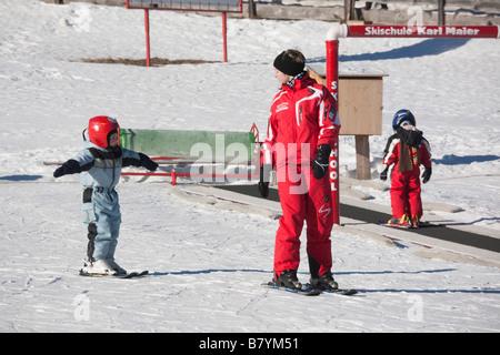 Rauris Austria Europe  Children learning to ski on ski-school nursery slopes in winter snow - Stock Photo