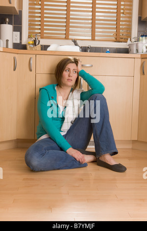 Woman sitting on the floor of the kitchen - Stock Photo