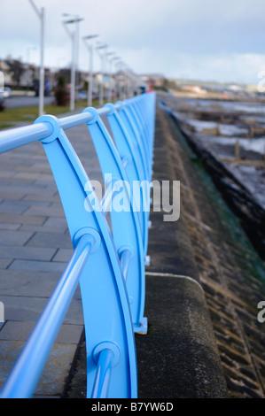 Blue iron railings along sea front at Carrickfergus - Stock Photo