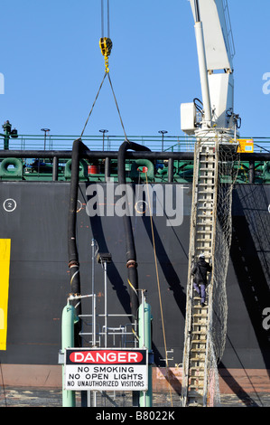 Offloading fuel from a tanker ship showing 2 hoses connected from ship to shore with single man climbing up long - Stock Photo