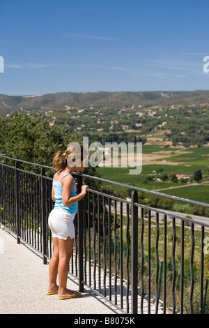 Little 8 years old girl looking at the sight from a terrace. La Cadière d'azur, Var, Cote d'Azur, 83, France - Stock Photo