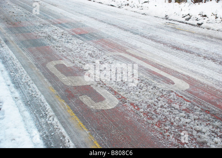 stop sign painted on a snowy road - Stock Photo