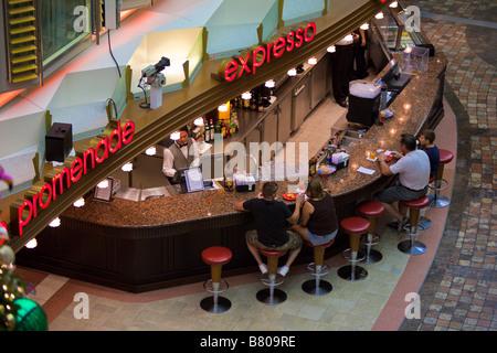 Cruise passengers sit at Expresso bar on Royal Promenade deck of Royal Caribbean Navigator of the Seas cruise ship - Stock Photo