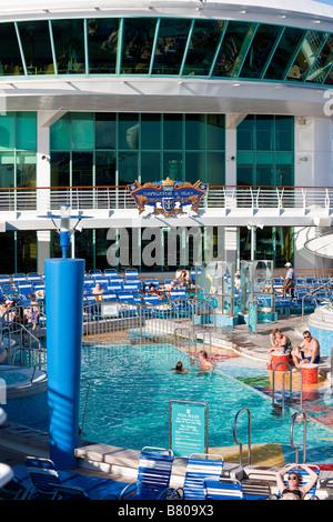 Sunbathers lounge around pool on Royal Caribbean Navigator of the Seas cruise ship - Stock Photo