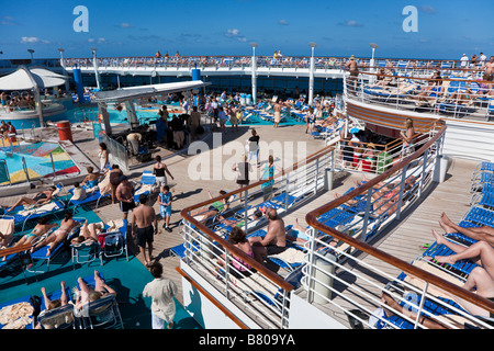 Cruise ship passengers lounging on the sun deck around the pool on Royal Caribbean Navigator of the Seas - Stock Photo