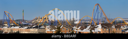 Panorama of a closed amusement park Wonderland roller coaster in winter next to a residential housing development - Stock Photo