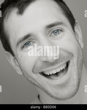 Portrait of a widely smiling handsome young man - Stock Photo