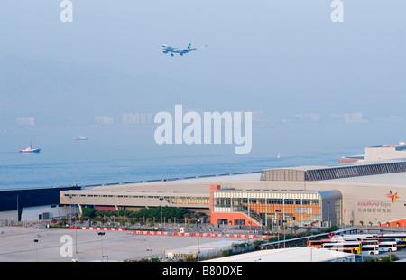 An airplane arrives at Hong Kong Chek Lap Kok Airport next to Asia World Expo in Hong Kong - Stock Photo