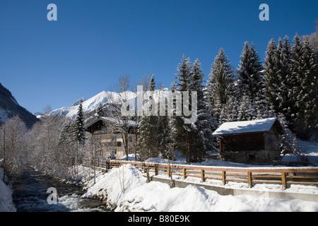 Pinzgau Region Austria EU January View across the Rauriser Ache River in snow covered Rauriser Sonnen valley - Stock Photo