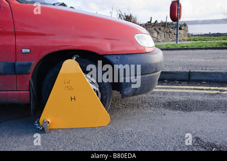 Yellow parking/wheel clamp on the front wheel of a red car parked on double-yellow lines. - Stock Photo