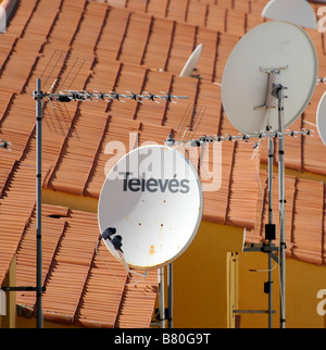 Television aerials and signal reception satellite dishes situated on rooftop of spanish properties - Stock Photo