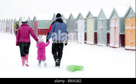 View of family group and snow covered beach huts on Brighton Beach, UK - Stock Photo