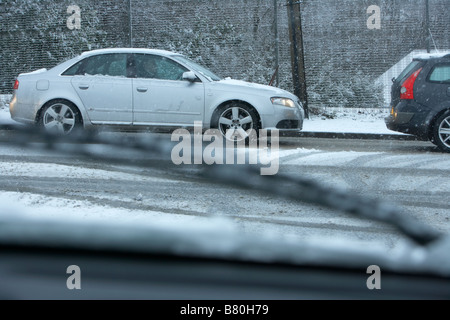 looking through car windscreen during snowstorm at queue of cars sitting in snowy treacherous driving conditions - Stock Photo