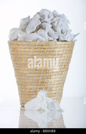 wicker waste paper basket bin full of used tissues with single used tissue lying in front of bin - Stock Photo