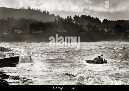 A Coast Guard rescue boat enters the harbor at Depoe Bay on the Oregon Coast in stormy weather - Stock Photo